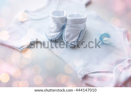 baby clothes, babyhood, motherhood and object concept - close up of white bodysuit, bootees and soother for newborn boy on table - stock photo
