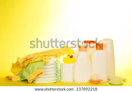 Baby clothes, diapers and children's cosmetics on a yellow background
