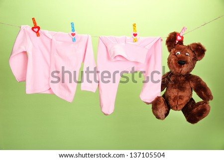 Baby clothes hanging on clothesline, on color background - stock photo