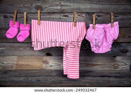 Baby clothes hanging on clothesline, on wooden background