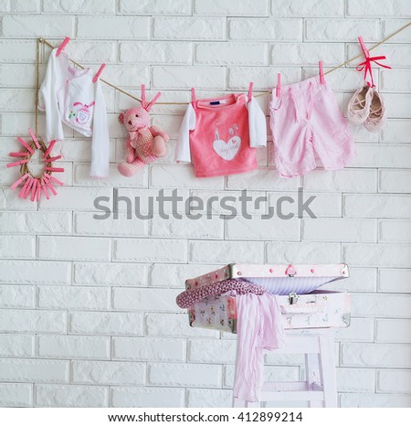 Baby clothes hanging on the wall as decoration of shooting location - stock photo