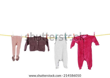 Baby clothes hanging on washing line - stock photo