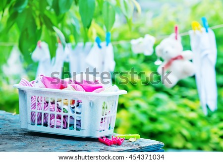 baby clothes on rope in the garden - stock photo