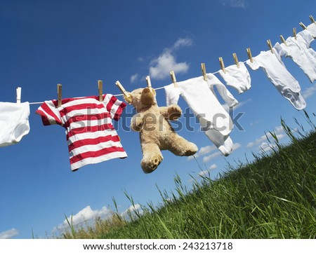 Baby Clothing and a teddybear on a clothesline towards blue sky - stock photo