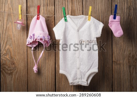 Baby clothing hanging on the clothesline on a wood background - stock photo