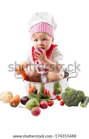 Baby cook girl wearing chef hat with fresh vegetables and fruits. Use it for a child, healthy food concept - stock photo