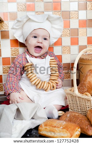 baby cook with bread and steering-wheels sits on a kitchen table - stock photo