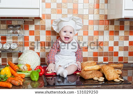 Baby cook with bread and steering-wheels sits on a kitchen table
