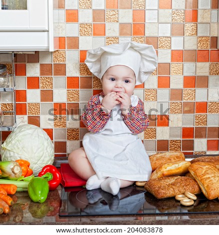 Baby cook with bread and vegetables sits on a kitchen table