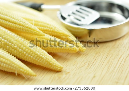 Baby corn for cooking on wood board, Baby corn, young corn, or cornlettes, is a cereal grain taken from corn (maize) harvested early while the stalks are very small and immature. - stock photo