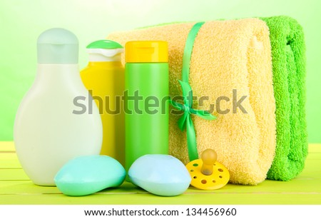 Baby cosmetics, soap and towels on wooden table, on green background