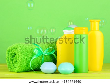 Baby cosmetics, towel and soap on wooden table, on green background