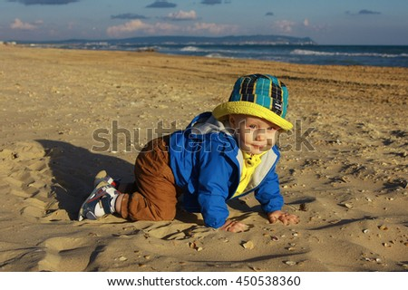 baby crawling on sand on background of blue sky and sea, happiness, copy space for text