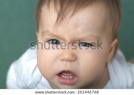 Baby crying portrait on green background - stock photo