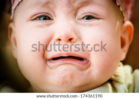 Baby crying - pure authentic emotion, tears visible - stock photo