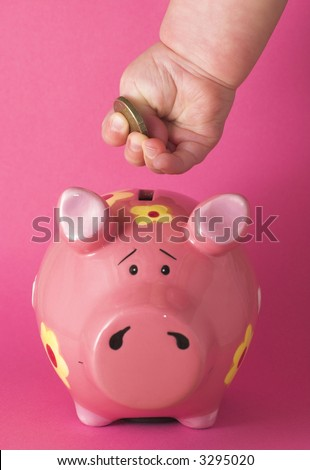 Baby deposits coin in cute pink piggy bank on a pink background.