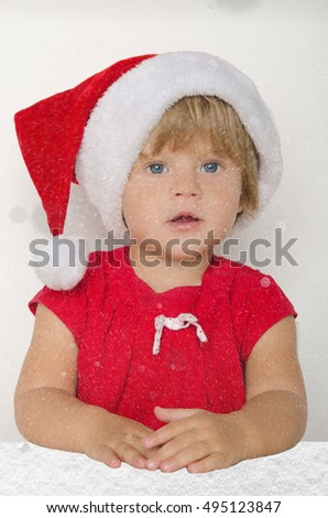 baby dressed as Santa under the falling snow on gray background