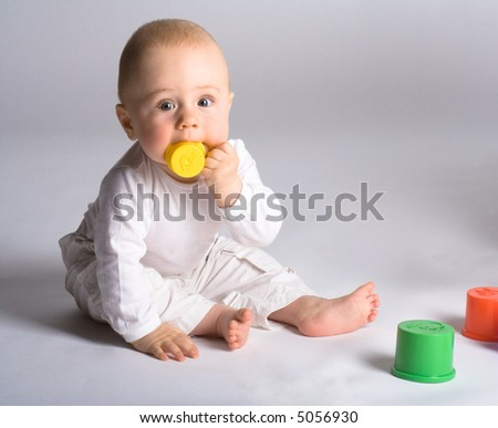 Baby dressed in white, sitting on floor, color plastic cups, biting on yellow cup