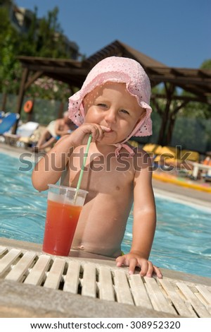 Baby drinking cocktail on swimming pool - stock photo