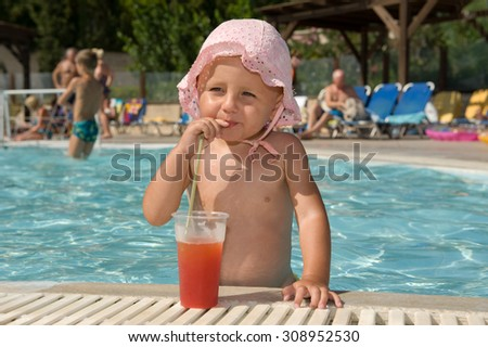 Baby drinking cocktail on swimming pool