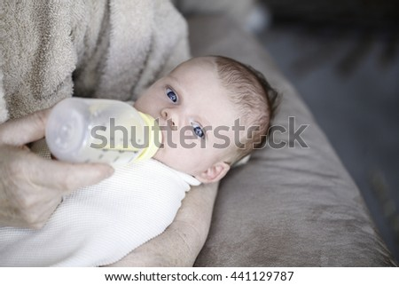 Baby drinking milk from bottle with nipple in mouth