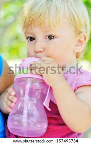 baby drinking water from bottle with straw - stock photo
