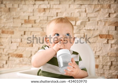 Baby drinking water in a chair on brick wall background - stock photo