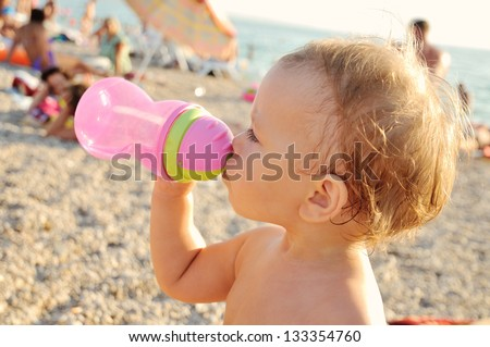 baby drinking water on the beach - stock photo