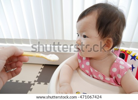 Baby eating baby food, yogurt