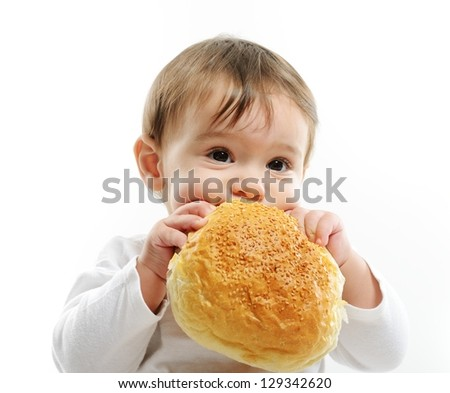 Baby eating bun bread - stock photo