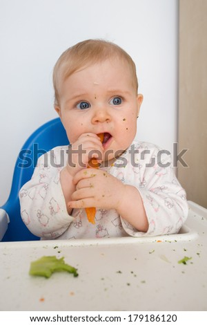 baby eating carrots at home, all soiled vegetables, healthy nutrition of infants
