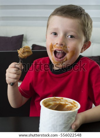 Baby eating chocolate in spoon.