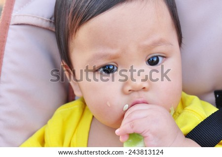baby eating cucumber - stock photo