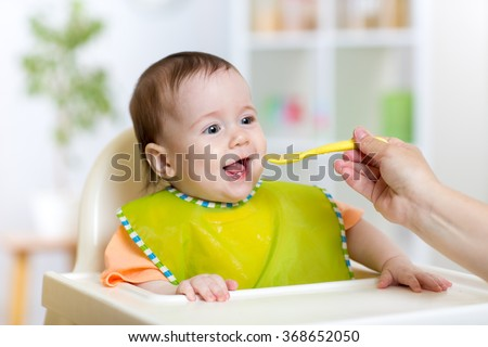 baby eating food on kitchen - stock photo