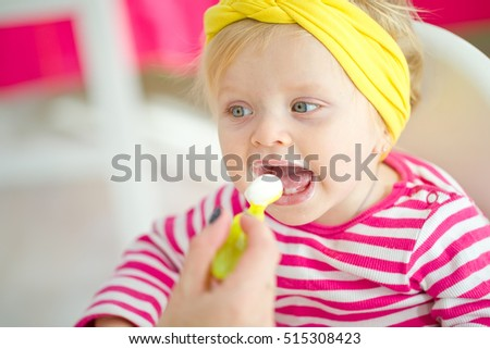 baby eating food on kitchen