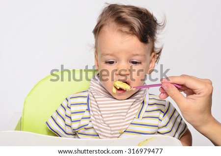 Baby eating food with a spoon, toddler eating messy and getting dirty, infant having oatmeal as breakfast, parent hand feeding his child