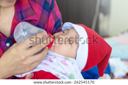 Baby eating milk from the bottle on Mother Feeds Her Newborn Baby, Feeding Baby - stock photo