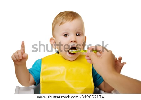 Baby eating spoon baby food jar.  Child feeding. Giving fruit sauce to baby boy. Child sitting in chair with a spoon Spoon-feeds the child - stock photo
