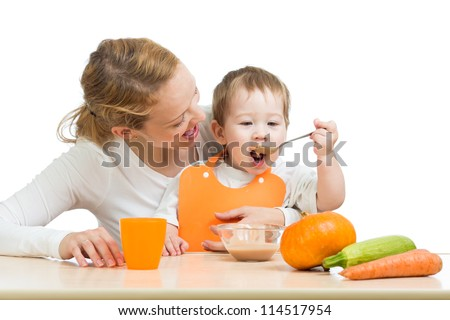 baby eating vegetables puree by spoon and sitting on mother laps - stock photo
