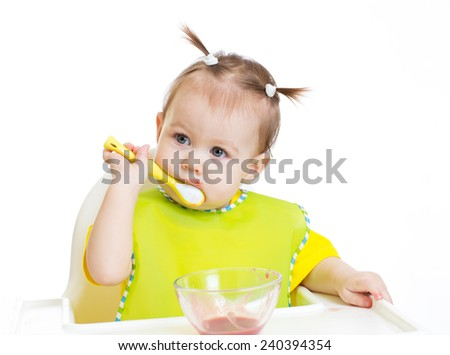 Baby eating with appetite sitting at table
