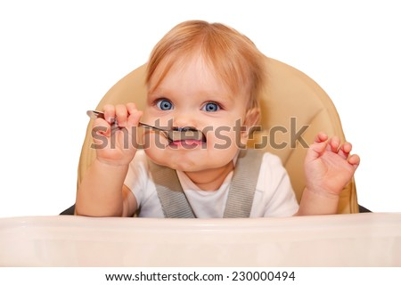 Baby eating with spoon and sitting in a high chair for feeding. Isolated on white background. - stock photo