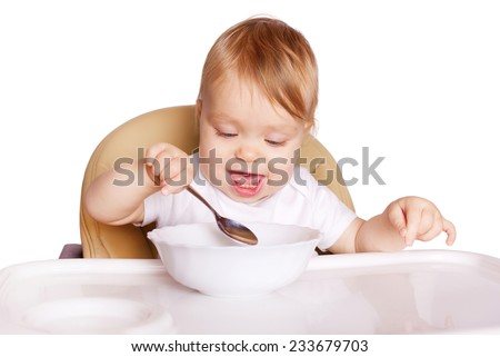 Baby eating with spoon and sitting in high chair for feeding. Healthy food and eating. Isolated on white background.