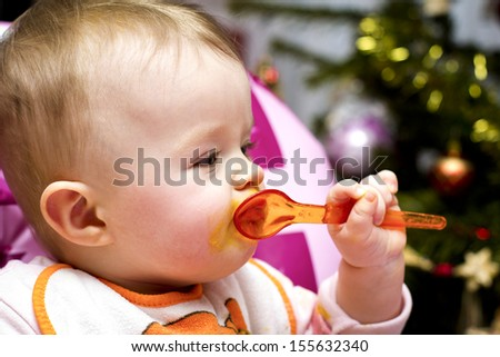 Baby eating with spoon at Christmas - stock photo