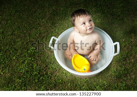 Baby enjoying his bath outdoors, high angle view - stock photo