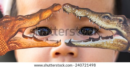 Baby eyes are staring at the open mouth of the crocodile both. - stock photo