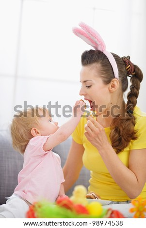 Baby feeding mother Easter biscuits - stock photo