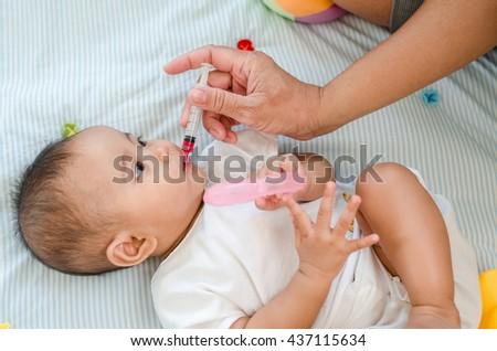 Baby feeding with liquid medicine - stock photo