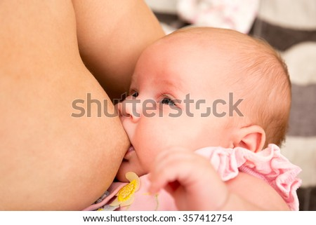 Baby feeds on mother's breasts milk. Infant baby girl is suckling - stock photo