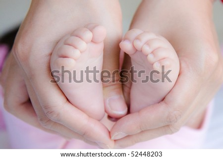 baby feet are held in mommy's hands tightly - stock photo
