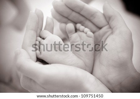 Baby feet cupped into mothers hands. - stock photo